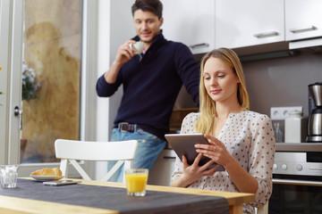 frau sitzt in der küche und liest am tablet