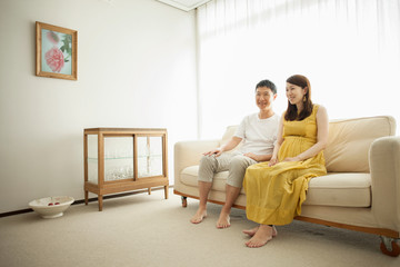 Man and pregnant woman sitting on sofa