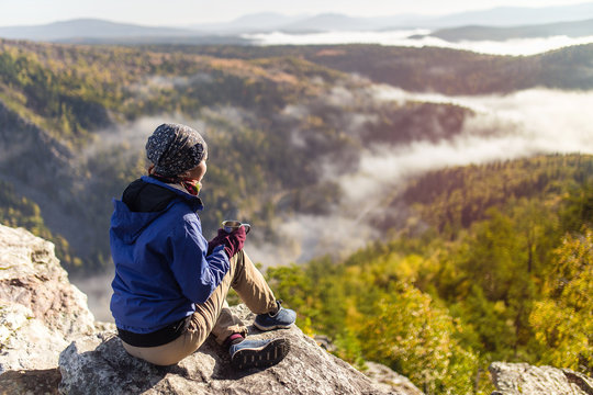 tourist young woman is sitting with a mug of tea on a cliff overlooking the autumn mountains with fog. The concept of a happy holiday in the nature, Hiking
