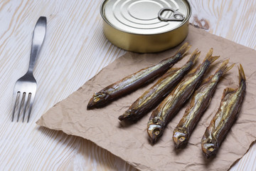 Smoked capelin and conserve tins on wooden background