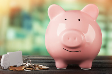 Piggy bank style money box on wooden table on bright background