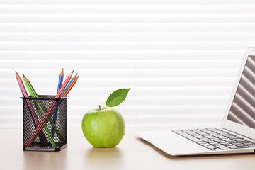 Office workplace with laptop, apple and pencils