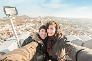 Lovers do selfie on the roof of the town hall.