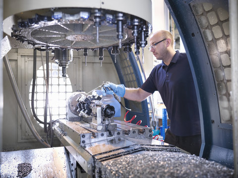 Engineer cleaning computer numerical controlled (CNC) lathe in factory