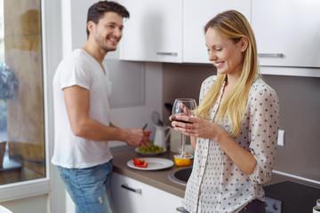 glückliches paar steht in der küche und bereitet das abendessen vor