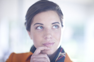 Businesswoman with hand on chin, looking up