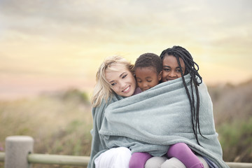 Gay couple and child wrapped in blanket