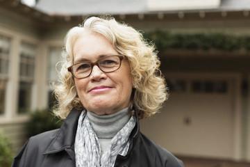 Portrait of happy senior woman outside house