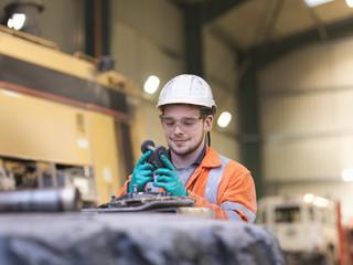 Apprentice engineer inspecting equipment in surface coal mine
