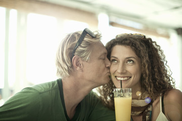 Young couple kissing in cocktail bar