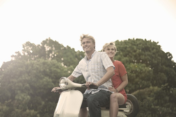 Young couple riding moped