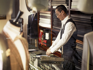 Tailor working at counter in tailors shop