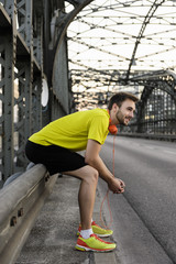 Young male runner resting on bridge