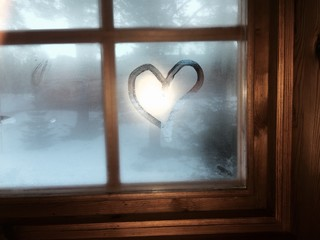 Heart on moisture window. Interior cabin winter view.