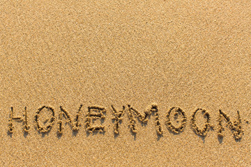Honeymoon - written manually on the texture of sea sand.