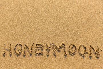 Honeymoon - written manually on the texture of sea sand.