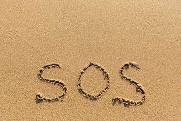 SOS - written manually on the texture of sea sand.