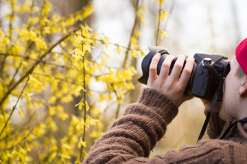 Young man / teenager with red hat taking a nature photo of beaut