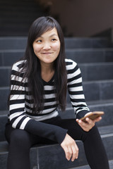 Mid adult woman sitting on steps holding smartphone