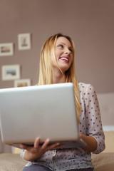 lachende frau mit laptop in ihrer wohnung