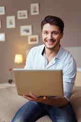 mann sitzt auf dem bett und hält laptop in der hand
