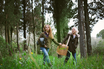 Mother and teenage daughter carrying picnic basket
