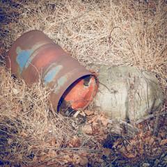 Old rusty metal oil drum, rusting in a field