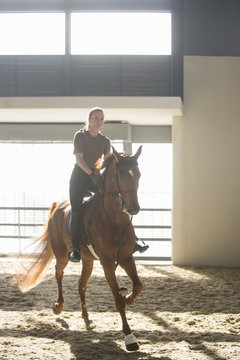 Woman trotting on chestnut horse in indoor paddock