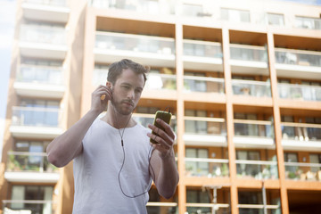 Man listening to music on headphones, building in background