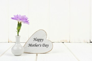 Happy Mother's Day heart tag with small vase and single purple carnation flower against a white wood background