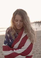 Young woman wrapped in american flag on beach, Santa Monica, California, USA