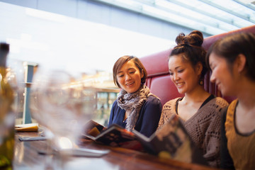 Young women reading menus in cafe
