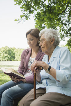Senior woman and granddaughter sitting on park bench reading bible