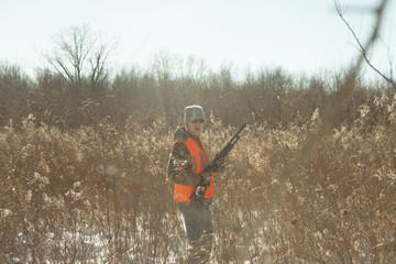 Teenage boy hunting with shotgun in Petersburg State Game Area, Michigan, USA