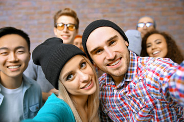 Young people taking group photo on brick wall background