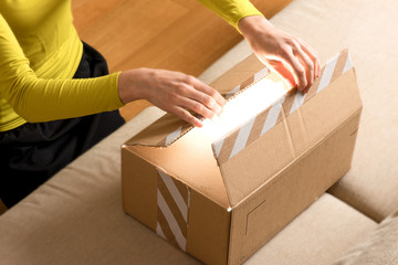 woman opening cardboard box at home, online shopping