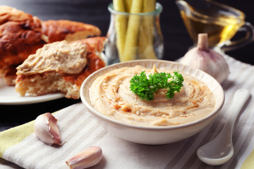 Ceramic bowl of tasty hummus with parsley and cucumber on table
