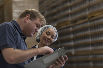 Factory worker and manager looking at clipboard in warehouse