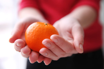 Female hands holding a tangerine, closeup