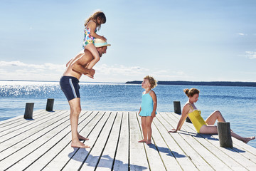 Parents and two young girls on pier, Utvalnas, Gavle, Sweden