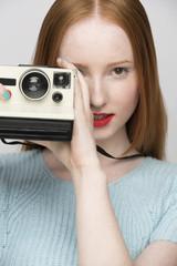 Young woman holding polaroid camera