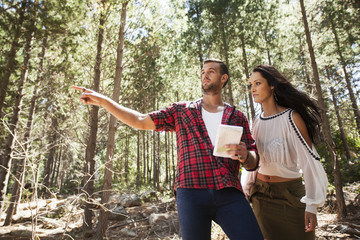 Young couple in forest, man pointing