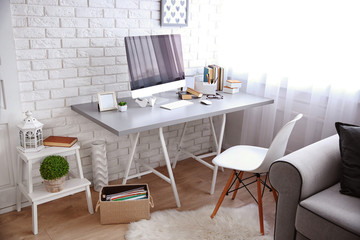 Modern interior. Comfortable workplace. Table with computer on it against white brick wall