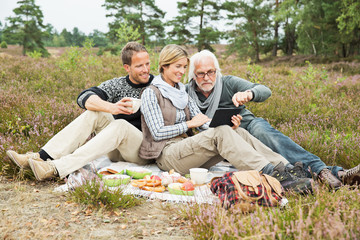Senior man and mid adult couple having picnic