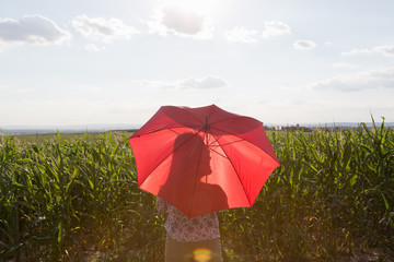 Woman standing holding red umbrella