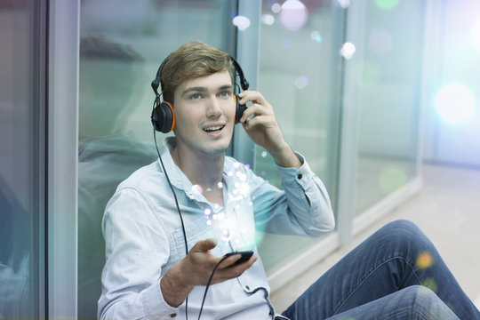 Young man with headphones and smartphone with lights coming out of it