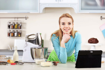 Young woman using a tablet computer to follow a recipe