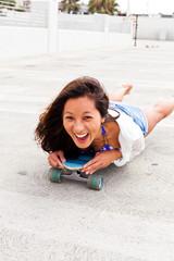 Woman in parking lot lying on skateboard