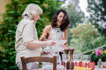 Mother and adult daughter setting table for family meal