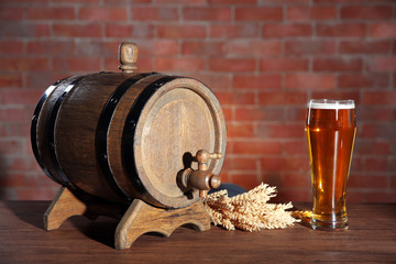 Papiers peints Affiche vintage Glass of light beer with wooden barrel and barley ears on brick wall background